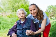 Assisted living. Senior invalid woman spending time outdoor with friendly young caregiver royalty free stock photos