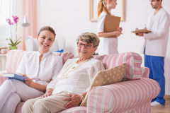 Assisted living for seniors. Clinic interior with senior patient on a couch and nurses standing behing royalty free stock images