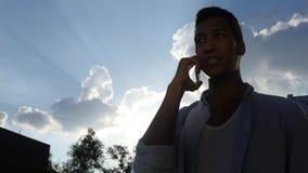 Assistendo alla telefonata, davanti al Sun durante il tramonto, siluetta Fotografia Stock Libera da Diritti