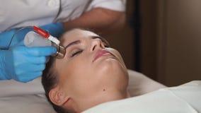 Assistent som förbereder framsidan för kvinna` s för icke-injektion en mesotherapy behandling arkivfilmer