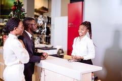 Assistente africano dell'autonoleggio che fornisce informazioni ad un cliente delle coppie immagini stock
