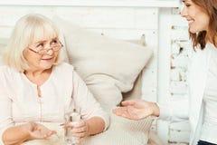 Assistente amigável do trabalho social que recomenda comprimidos ao pensionista em casa fotos de stock