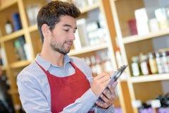 Assistente das vendas que faz a contagem do inventário na loja fotografia de stock