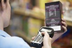 Assistente das vendas que verifica os níveis conservados em estoque em Supmarket usando a mão ele fotos de stock