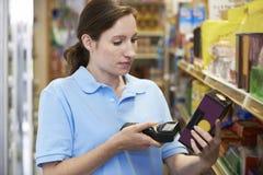 Assistente das vendas que verifica os níveis conservados em estoque em Supmarket usando a mão ele imagens de stock