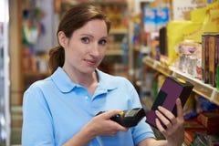 Assistente das vendas que verifica os níveis conservados em estoque no supermercado usando a mão ele foto de stock royalty free