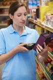 Assistente das vendas que verifica os níveis conservados em estoque no supermercado usando a mão ele fotos de stock