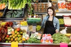 Assistente de compra que pesa frutas e legumes na loja de mantimento foto de stock royalty free