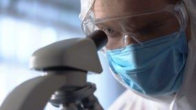 Assistente de laboratório masculino na máscara protetora e eyewear usando o microscópio para a pesquisa fotografia de stock royalty free