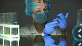Assistente de laboratório que põe sobre luvas, prevenção de acidentes durante o trabalho com produtos químicos filme