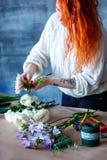 Assistente de loja fêmea alegre encantador que faz o ramalhete com açafrão roxo Imagens de Stock