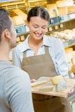 Assistente de loja que mostra queijos da bandeja do cliente foto de stock