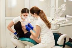 Assistente del briciolo di medico che tratta i denti del paziente, impedicenti la carie Concetto di stomatologia fotografie stock libere da diritti
