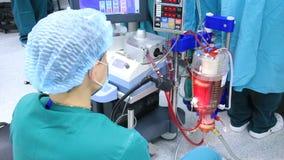 Assistente della chirurgia che fa funzionare macchina cuore-polmoni archivi video