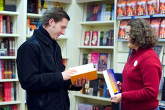 Assistente della libreria ed il cliente fotografie stock