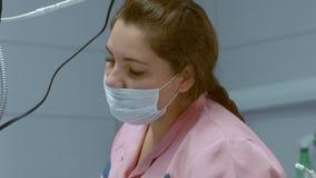 Assistente dentario nella maschera durante la ricezione del paziente archivi video