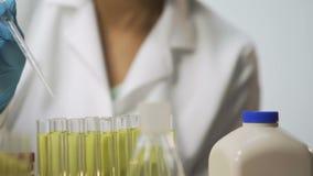 Assistente di laboratorio che controlla materiale biologico sui virus facendo uso della pipetta stock footage