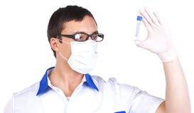 Assistente di laboratorio che controlla una provetta Fotografia Stock
