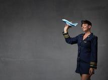 Assistente di volo che plaing con un aereo del giocattolo Immagine Stock