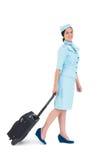 Assistente di volo grazioso che cammina con la valigia Immagini Stock Libere da Diritti