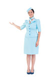 Assistente di volo grazioso che mostra con la mano Immagine Stock