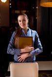 Assistente di volo sorridente di posa del ristorante alla moda Immagine Stock