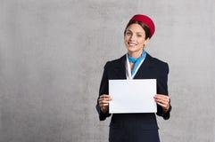 Assistente do voo que guarda o sinal branco imagem de stock royalty free