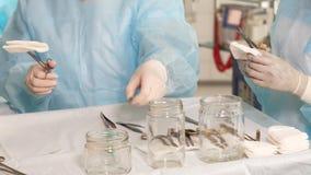 Assistente maschio che prepara gli strumenti medici per realizzare operazione video d archivio