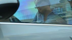 Assistente masculino que dá auto chaves à mulher de negócio ocupada que apressa-se à reunião video estoque