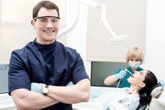 Assistente que trata os dentes cariados do paciente Foto de Stock Royalty Free