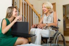 Assistente social e mulher deficiente com portátil Fotos de Stock Royalty Free