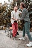 Assistente social seguro que ajuda a paciente deficiente a levantar-se foto de stock royalty free