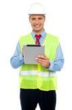 Assistente tecnico di costruzione maschio che per mezzo del pc del ridurre in pani fotografia stock libera da diritti