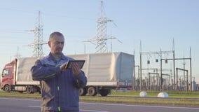 Assistente tecnico ed operaio alla sottostazione elettrica Lavoratore con la compressa e la lavagna per appunti nella riunione al video d archivio