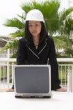 Assistente tecnico femminile che si leva in piedi al computer portatile Immagini Stock