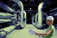Assistente tecnico femminile con le cianografie sulla fabbrica Immagine Stock