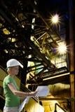 Assistente tecnico femminile con le cianografie sulla fabbrica fotografie stock libere da diritti