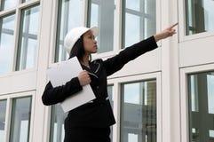 Assistente tecnico femminile nell'indicare del cappello duro Fotografia Stock Libera da Diritti