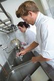Assistentes da cozinha que lavam pratos imagem de stock royalty free
