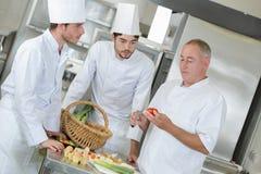 Assistentes de observação do cozinheiro chefe principal que decoram o prato imagem de stock royalty free