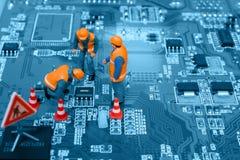 Assistenti tecnici miniatura che riparano errore sul chip Fotografie Stock