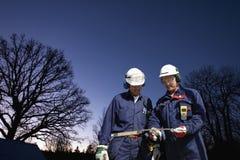 Assistenti tecnici sotto il cielo di sera Fotografia Stock Libera da Diritti