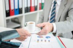 Assistenz-Angebotkaffee zu ihrem Chef Stockfotografie