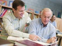 assistenza dell'insegnante privato maturo dell'allievo delle biblioteche Immagini Stock Libere da Diritti