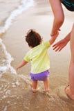 Assistere al bambino sulla riva di mare Fotografia Stock