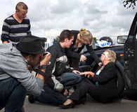 Assisting. Bystanders assisting a wounded woman after a car crash whilst a press photographer takes pictures Stock Image