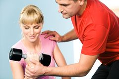 Assisting. Image of pretty girl exercising with barbell in hand while the trainer assisting her Royalty Free Stock Images