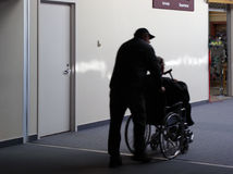 Assisting the Physically Challenged. A skycap wheels an elderly passenger through the concourse. Silhouette, motion blur on the skycap and passenger royalty free stock images
