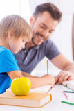 Assisting son with schoolwork. Stock Photography