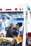assistting sårad paramedicinsk kvinna Arkivfoton